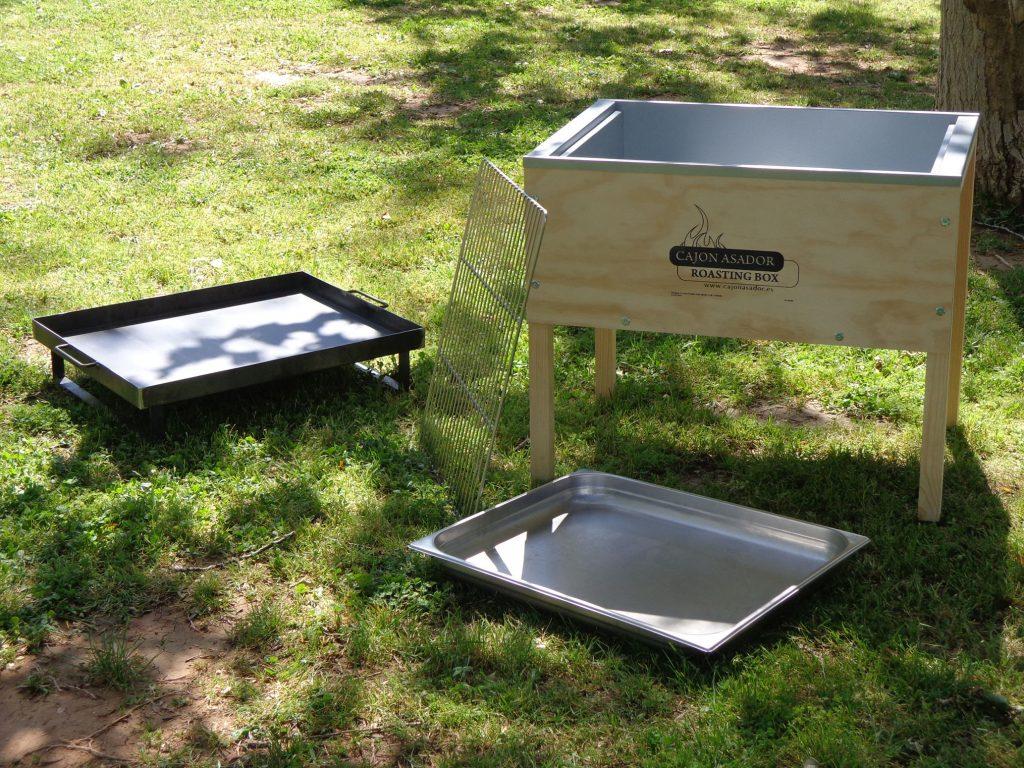 Se observan las partes suministradas: El cajón Asador en si, la bandeja de jugos, la parrilla y la bandeja de carbón